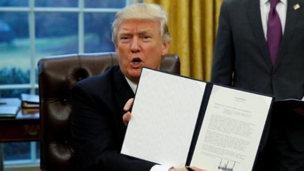 President Donald Trump holds up the executive order on withdrawal from the Trans Pacific Partnership after signing it in the Oval Office of the White House in Washington January 23, 2017.